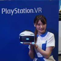 That's using your head: A woman holds up a virtual reality helmet at the Tokyo Game Show on Sept. 15.   JASON COSKREY