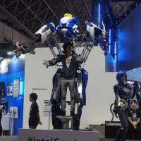 Suiting up: A man wears a mechanized suit from Intel at the Tokyo Game Show on Sept. 15.   JASON COSKREY