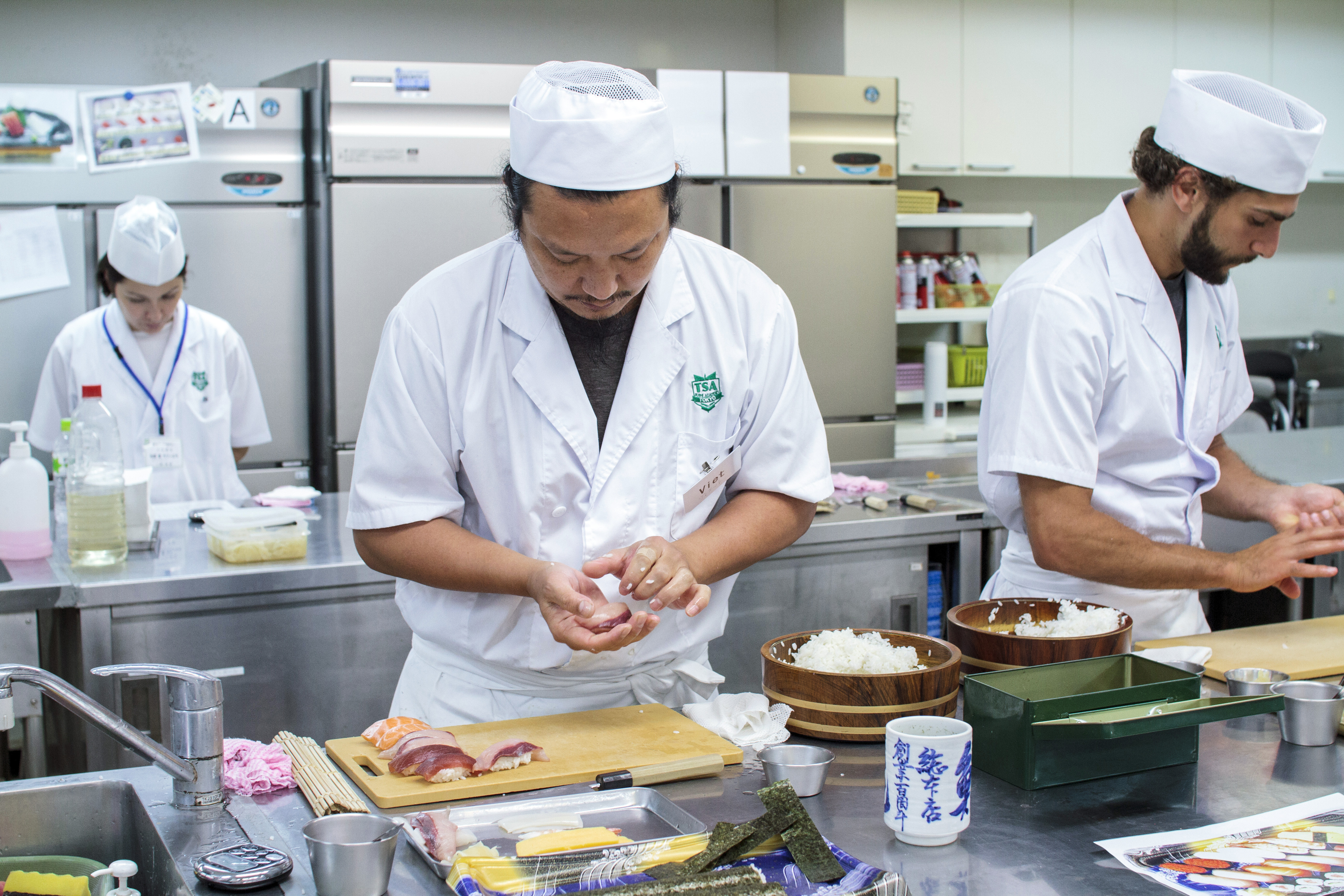 Pressure is on: International students Viet Tran (center) and Anthony Zeidan (right) prepare sushi rolls during a time trial at Tokyo Sushi Academy. | JAMES HADFIELD