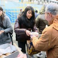 A student distributes food at a soup kitchen in Kotobukicho, Kanagawa Prefecture, on Dec. 30, 2015. | KYODO