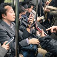 Communication cues: Commuters use smartphones and tablets in an underground train in March 2015.   ISTOCK