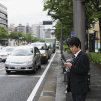 Technological limitations: A businessman sends a text message while waiting to cross a street in Kyoto.    ISTOCK
