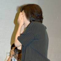 Publicly ashamed: Actress Atsuko Takahata covers her face at a news conference on Aug. 26 after apologizing for her son, who was arrested for a sexual assault. | KYODO