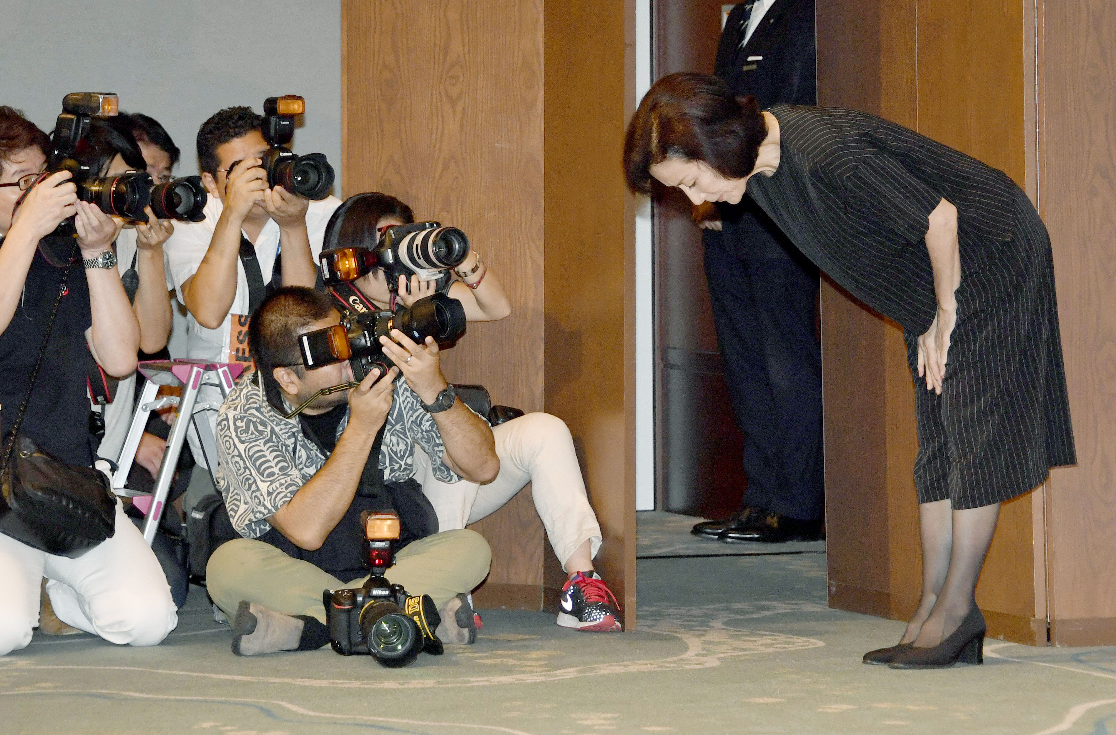 Actress Atsuko Takahata bows before photographers at a news conference on Aug. 26 after apologizing for her son, who was arrested for a sexual assault.  | KYODO