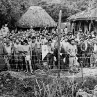 Ongoing struggles: Japanese prisoners stand in a makeshift jail on Okinawa in June 1945. Though the war is over, its effects linger. As former Prefectural Assembly member Keiko Itokazu says of life in modern Okinawa, 'It feels like we are at war.' | PUBLIC DOMAIN