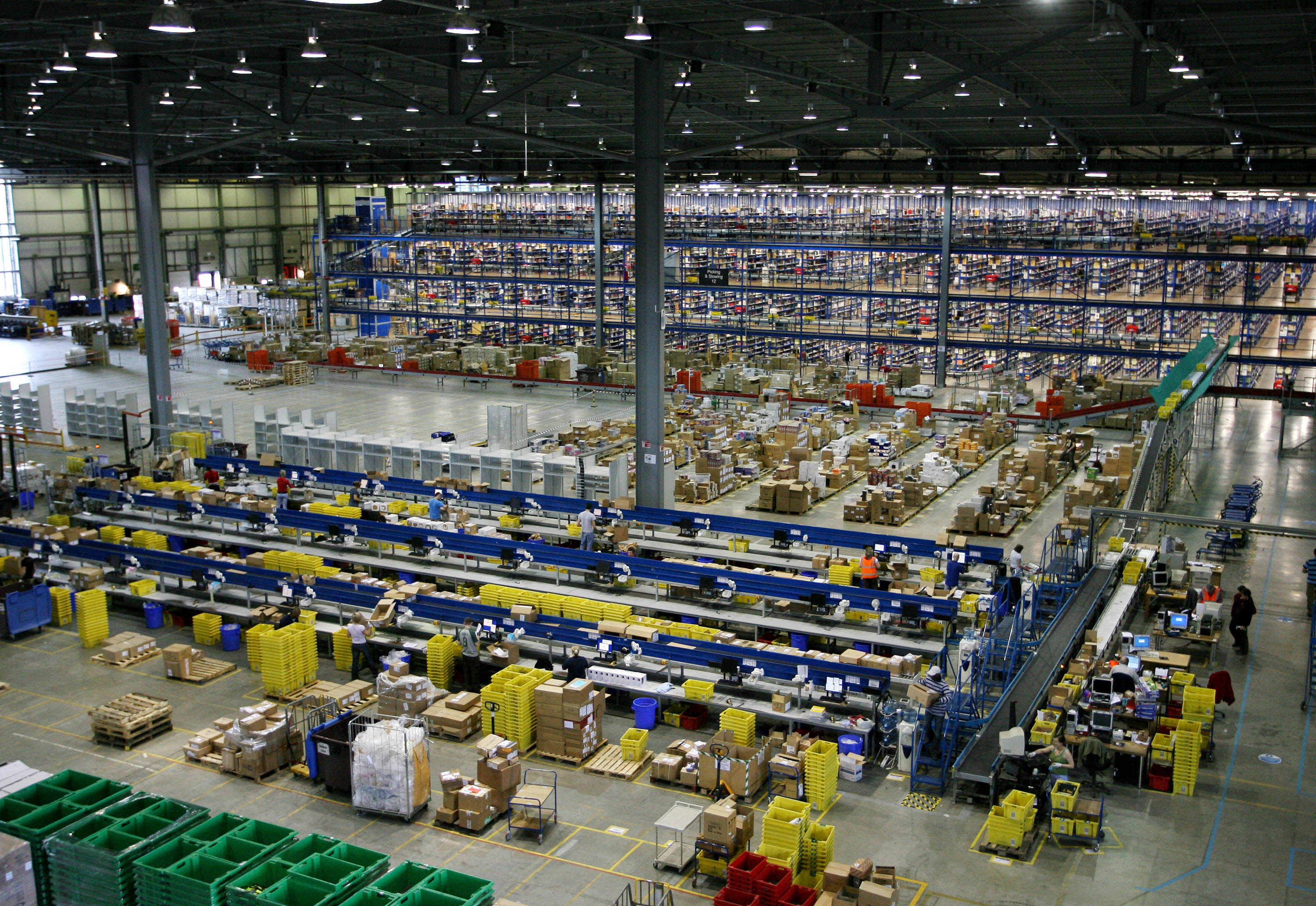 Economies of scale: Packers work at an Amazon warehouse in Milton Keynes, England. Japan's saihan seido pricing system may not be enough to save remaining bookstores, whose advantages Amazon.jp has systematically nullified over the years.   BLOOMBERG