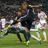 Japan forward Keisuke Honda shoots against United Arab Emirates goalkeeper Khalid Eisa during the UAE's 2-1 win in a World Cup qualifer in Saitama on Thursday. | AP