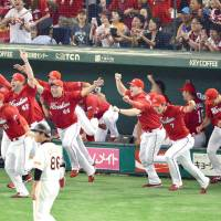 Hiroshima Carp players storm out of their dugout to celebrate the team's Central League pennant-clinching victory over the Yomiuri Giants on Saturday night at Tokyo Dome. | KYODO