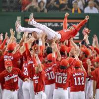 Carp manager Koichi Ogata receives a traditional doage (victory toss) after the team's pennant-clinching win on Saturday. | KYODO