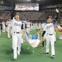 Fighters manager Hideki Kuriyama (right) and team members salute the team's fans while doing a victory lap with their  Pacific League  pennant at Sapporo Dome on Friday. Hokkaido Nippon Ham defeated the Chiba Lotte Marines 3-1 in the teams' regular-season finale. | KYODO