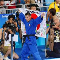 Japanese athletes grab medals on mat, in pool