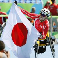 Tomoki Sato waves a Japanese flag after winning silver in the men's T52 400-meter wheelchair race at the 2016 Rio Paralympics on Tuesday. | KYODO