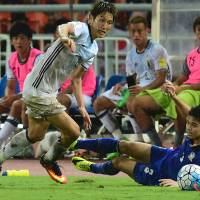 Japan's Genki Haraguchi (left) evades Thailand's Mika Chunuonsee during the 2018 World Cup football qualifying match between Thailand and Japan in Bangkok on Tuesday. | AFP-JIJI