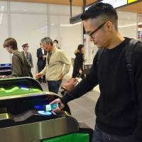 A man uses Apple Pay on his smartphone to get through a ticket gate at JR Shinjuku Station on Tuesday. The service began in Japan the same day. | KYODO