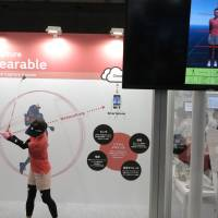 A model at Murata Manufacturing Co. wears an outfit equipped with motion sensors that let her to check her golf swing via a smartphone app. The show this year drew developers eager to collaborate with each other. | KAZUAKI NAGATA