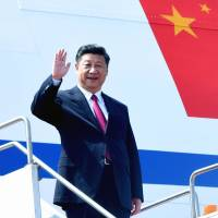 Chinese President Xi Jinping waves as he arrives in Dhaka on Friday. | AFP-JIJI