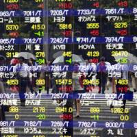 People are reflected on the electronic stock indicator of a securities firm in Tokyo Monday. Asian stocks were mostly higher Monday, with Chinese and South Korean trading closed, as investors weighed the prospects of a further U.S. interest rate hike and a report on business sentiment out of Japan. | AP