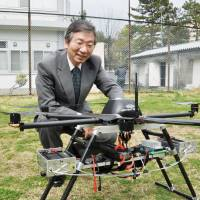 Kenzo Nonami, an engineering professor at Chiba University, displays a drone that his team developed for home deliveries. It aims to have a viable service in place by 2019. | KYODO