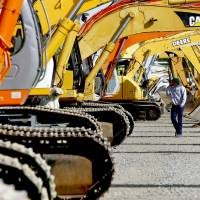 Hitachi excavators are sold at an industrial equipment auction in Dunnigan, California. Hitachi Construction Machinery Co. plans to buy Australia's Bradken Ltd., in its largest ever purchase. | BLOOMBERG