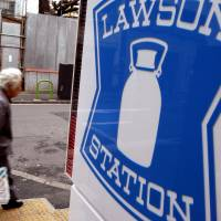 A pedestrian passes a Lawson convenience store in Tokyo. | BLOOMBERG NEWS