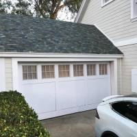 Tesla's electric car stands in front of a house with a Powerwall battery and a garage with a solar roof in Los Angeles on Friday. | REUTERS