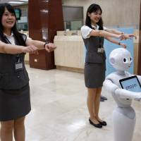 SoftBank's humanoid robot Pepper performs with employees at First Bank branch in Taipei on Thursday. | REUTERS