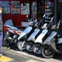 A passerby looks at Yamaha Motor Co. scooters outside a dealership in Tokyo. | BLOOMBERG
