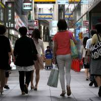 Women walk along a street in Kobe. The nation's spousal tax deduction system is in the spotlight, with some saying reforming it could help alleviate dwindling workforce numbers. | BLOOMBERG