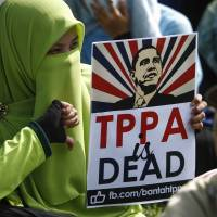 A Malaysian protester poses while holding a placard opposing the Trans-Pacific Partnership agreement and bearing U.S. President Barack Obama's image at a demonstration in Kuala Lumpur in January. | AP