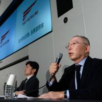 Tadashi Yanai (right), chairman and chief executive officer of Fast Retailing Co., speaks during a news conference in Tokyo on Thursday. The company reported its lowest income for the year to August since 2008. | BLOOMBERG