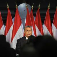 Hungarian Premier Viktor Orban looks at supporters before delivering a speech in Budapest on Sunday. Hungarians overwhelmingly supported the government in a referendum called to oppose any future, mandatory European Union quotas for accepting relocated asylum seekers but nearly complete official results show the ballot was invalid due to low voter turnout. | AP