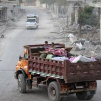 People who fled Islamic State areas travel on the back of a vehicle in al-Rai town, northern Aleppo countryside, Syria, Tuesday. | REUTERS