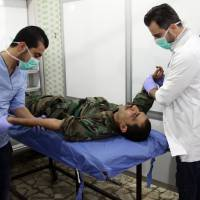 A Syrian man is treated at a hospital in a government-held area of Aleppo on Sunday following reports by state news agency SANA saying that rebels had fired shells containing toxic gas into regime-controlled parts of the northern embattled city.   AFP-JIJI