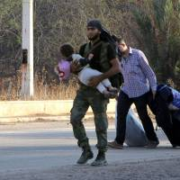A fighter carries a child near a man pulling belongings on Sunday as people leave Aleppo's southwestern front-line neighborhood of Dahiyet al-Assad, on the third day of a rebel offencive to break a three-month regime siege on the opposition-held east of Syria's second city.   AFP-JIJI