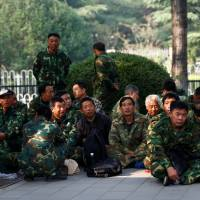 Uniformed people take part in a protest outside the Bayi Building, a major military building in Beijing, on Tuesday. | REUTERS