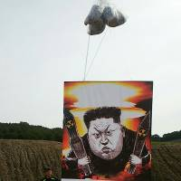 This handout photo released by North Korean defectors group, Fighters For Free North Korea (FFNK), on Friday shows a big banner with a caricature of North Korean leader Kim Jong Un as South Korean activists launch large balloons containing anti-Pyongyang leaflets into the air at a field near the Demilitarized Zone dividing the two Koreas in Paju. The banner reads: 'Down with manic Kim Jong-Un who fires nuclear missiles over our heads.' | FIGHTERS FOR FREE NORTH KOREA / AFP-JIJI