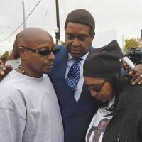 Attorney John Burris (center), comforts Robert and Deborah Mann, family members of Joseph Mann, who was killed by Sacramento police officers in July, following a news conference in the California state capital on Monday. | AP