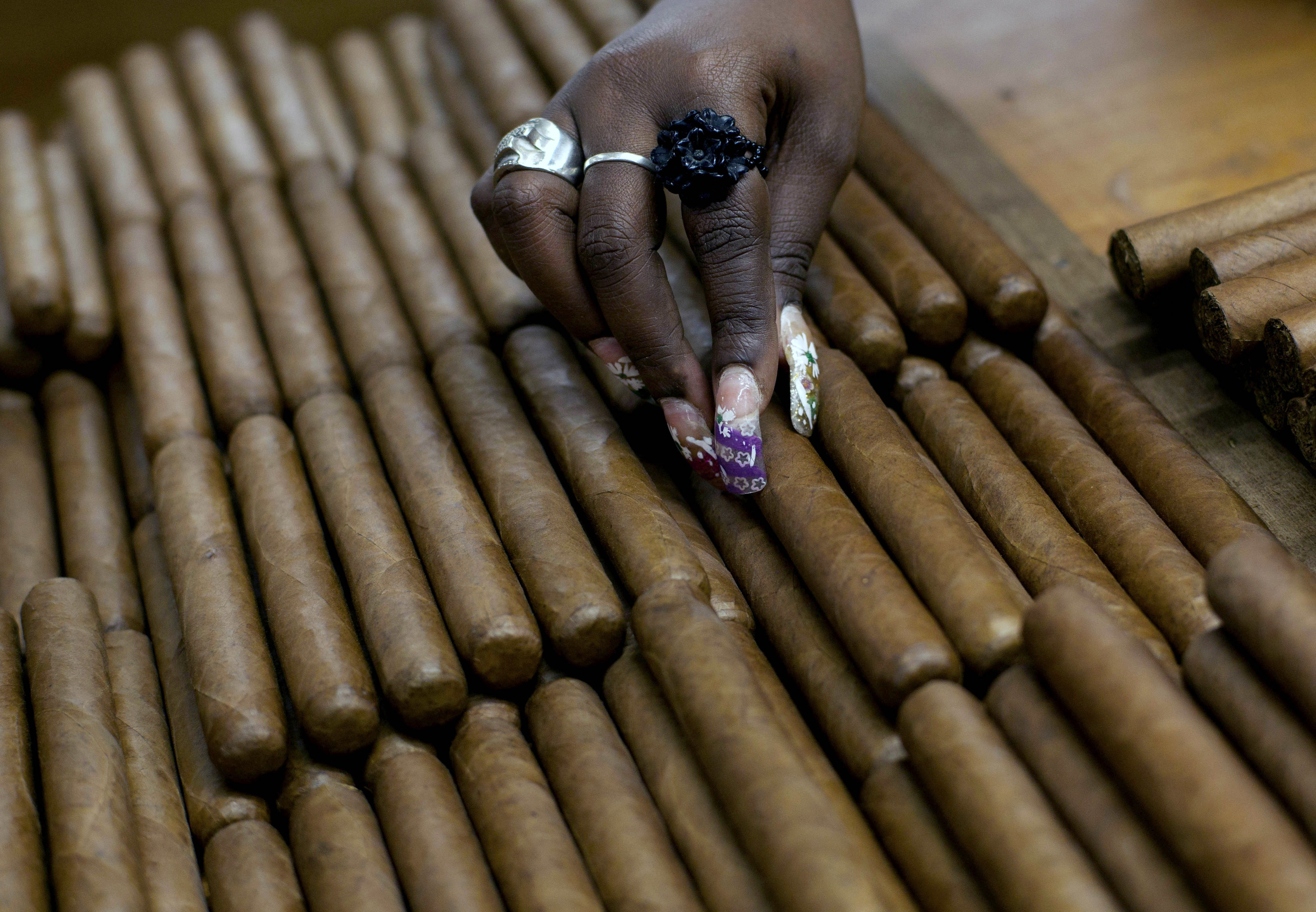A worker selects cigars at the H. Upmann cigar factory in Havana in March 2013. The Obama administration announced Friday it is eliminating a $100 limit on the value of Cuban rum and cigars that American travelers can bring back from the island.   AP
