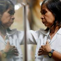 A woman prays after Mass in a chapel at Camp Crame, the headquarters of Philippine National Police, in Manila on Sunday. | REUTERS