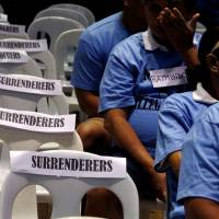 Filipinos accused of using and selling illegal drugs wait for fellow 'surrenderees' before taking a pledge not use or sell 'shabu,' or crystal meth, again after surrendering to police and government officials in Makati, Metro Manila, in August. | REUTERS