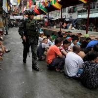 People sit on a street after they were rounded up as they wait to be brought to a police station for verification if they are involved with drugs, after police sources and local media reported that people were killed during a raid, in Manila Oct. 7. | REUTERS