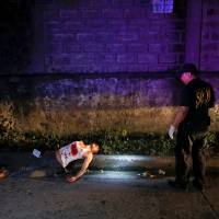 A policemen inspects the scene of the body of a man, who police said was a drug dealer shot dead during a drug buy-bust operation, along a street in Quezon city, Metro Manila, early Oct. 8. | REUTERS