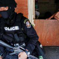 A baby looks at an armed member of a police SWAT team during a drug raid in Manila Oct.7. | REUTERS