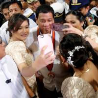 Philippine President Rodrigo Duterte has his picture taken together with three girls during a ceremony marking the anniversary of the Philippine Coast Guard in Manila on Oct. 12. | REUTERS