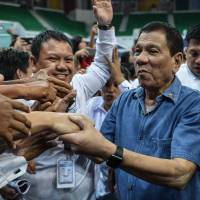 Philippine President Rodrigo Duterte shakes hands with Philippine nationals living in Brunei after delivering a speech during an official visit to the country Sunday. | AFP-JIJI