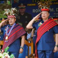 Philippine national police chief Ronald Dela Rosa (center) and other police officials wearing Igorot tribe headdresses salute on Sept. 2 during a visit to Camp Dangwa in Benguet province. | REUTERS