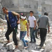 Syrians walk over rubble following airstrikes on the rebel-held Fardous neighborhood of the northern embattled Syrian city of Aleppo on Wednesday.   AFP-JIJI