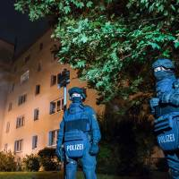 Policemen stand in front of a residential building in Chemnitz, eastern Germany, on Saturday. Police found several hundred grams of 'explosive materials' in the east German apartment of a Syrian man suspected of planning a terrorist attack, and arrested three people connected to him. The suspect, 22-year-old Syrian refugee Jaber Albakr, who was later captured, could have had 'an Islamist motive,' sources close to the police said. | AFP-JIJI