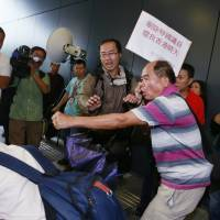 A pro-democracy protester (left) falls during a scuffle with pro-Beijing supporters (right) outside the Legislative Council in Hong Kong on Wednesday. | AP