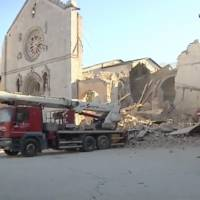 A man stands in front of a damaged church in Norcia, Italy, in this photo taken from video after a powerful earthquake with a preliminary magnitude of 6.6 rocked the country Sunday. | AP